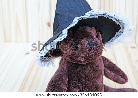 Front and slightly to the left view of the dark brown bear,wears white lace edge and black witch hat,on wood background - stock photo