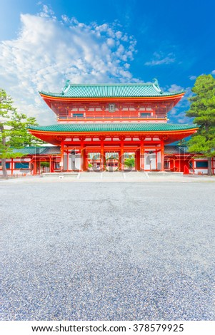 Front centered view of large red Tower Gate Ro-Mon at the chinowa-kuguri decorated entrance of Heian Jingu Shrine on a clear, blue sky day in Kyoto, Japan. Vertical - stock photo