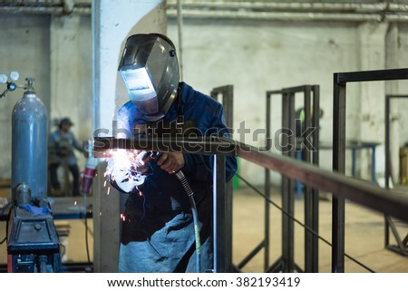 front close-up of a worker wearing protective gear, with mask and a leather apron, welding together two pieces of square pipes into a frame, with several frames already welded in the background - stock photo