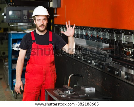 front close-up of a worker, with his left hand raised, showing his left ring finger missing, wearing red overalls, and a white protective helmet - stock photo