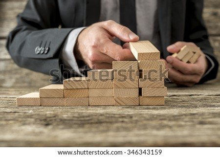 Front closeup view of businessman constructing steps of wooden pegs with focus to the peg in his hand, shallow dof. - stock photo