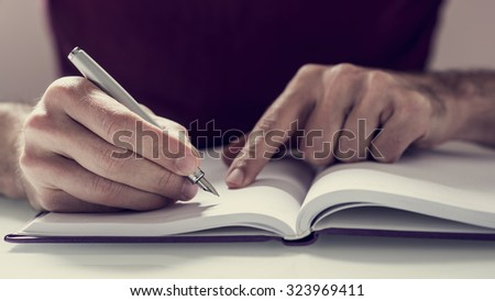 Front closeup view of male student writing notes with fountain pen in his notebook, with retro faded effect. - stock photo