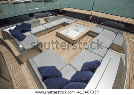 Front deck relaxation area of a large luxury motor yacht with seating area and jacuzzi - stock photo