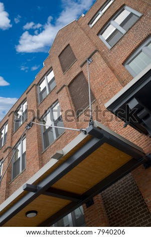 front detail of an urban Brick building with a blue sky and clouds