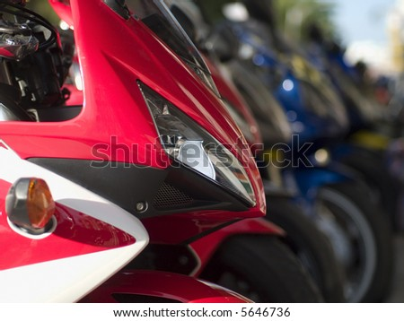 Front detail of heavy motorbike. Long row of blurred motorbikes in the background.