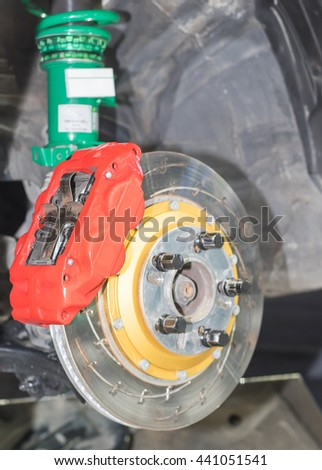 Front disk brake system on car in process of damaged tyre replacement. The rim is removed showing the front rotor and caliper. - stock photo