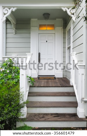 Front door and porch of a Victorian house or cottage - stock photo
