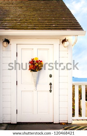 Front door of a seaside cottage painted white with vintage hardware and decorated with a basket of flowers.  - stock photo