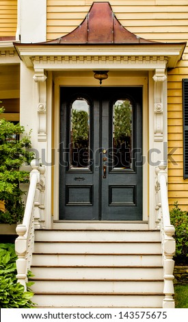 Front door of a vintage yellow house with white trim and a copper gable over the entry - stock photo