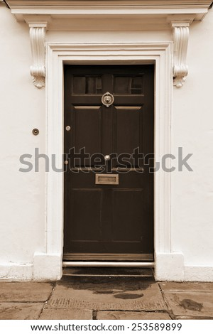 Front Door of an Old English Town House in Sepia - stock photo