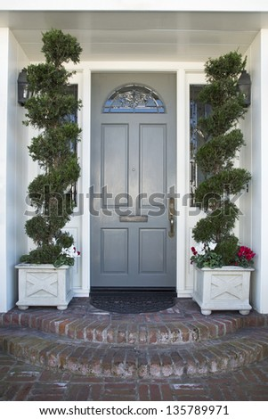 Front Door of an upscale home/Vertical shot of a blue front door with view of plants, brick steps, door mat and mail slot.