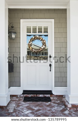 Front door of an upscale home/Vertical shot of a white front door on an upscale home with a wreath, brick, and reflection in the windows - stock photo