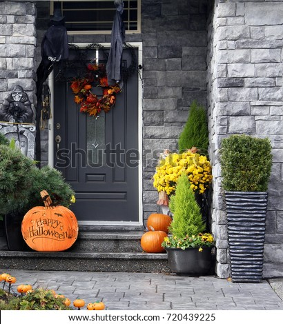 Front door to a house decorated with Halloween pumpkins