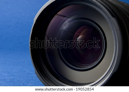 Front elements of a lens on the right-hand side of a blue background providing copy space