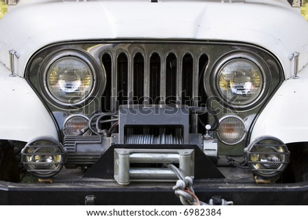 Front end, headlights and grille on a vintage four-wheel drive vehicle. - stock photo