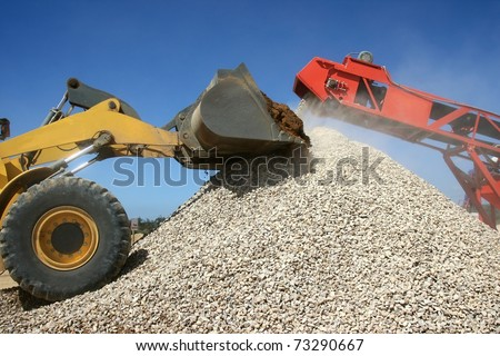 Front end loader and conveyor belt on a pile of graded stone - stock photo