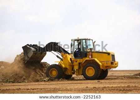 Front end loader clearing a construction site - stock photo