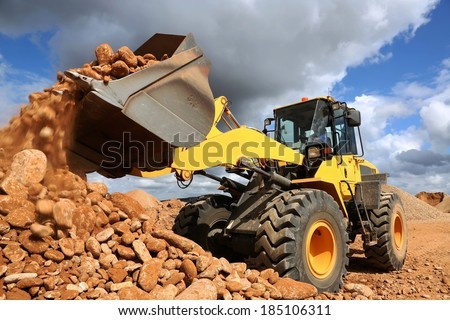 Front end loader dumping stone and sand in a mining quarry - stock photo