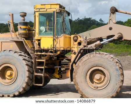 Front end loader loading gravel into a pick-up vehicle - stock photo