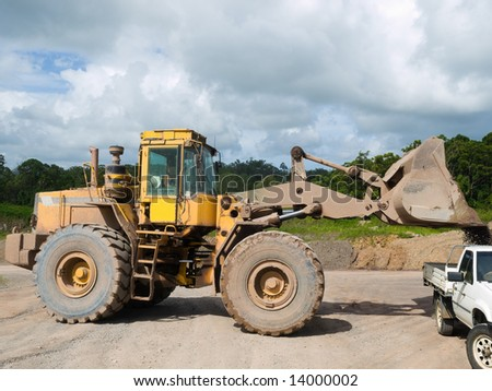 Front end loader loading gravel into a work pick-up vehicle - stock photo