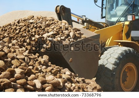 front end loader machine scooping up big stones in a quarry - stock photo