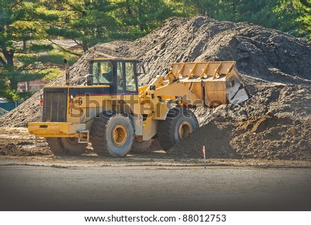 Front end loader moving piles of dirt on a construction site - stock photo