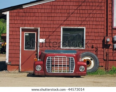Front end of red, vintage truck, leaning against an old building. - stock photo