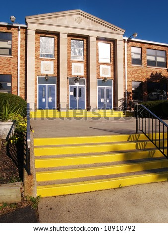 front entrance and steps for an old catholic high school - stock photo