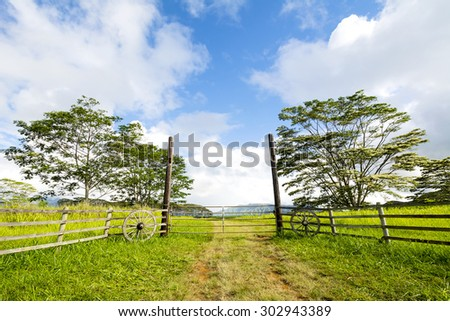 Front entrance gates to a countryside ranch in Kauai Hawaii are adorned with old wagon wheels to provide a western motif.  - stock photo