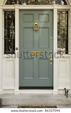 Front entrance to a home with classic design. The door has a large brass knocker and an elegant frame. Vertical shot.
