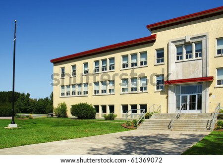 Front entrance with flag post of school building, could be small hospital, retirement home. - stock photo