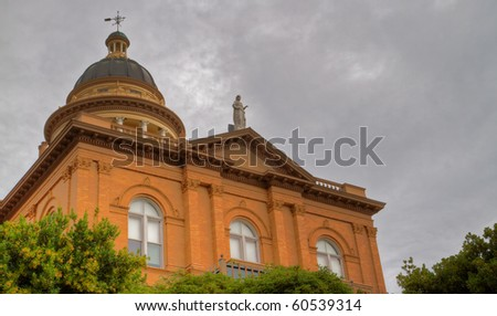 Front facade of pillared tan brick courthouse with statue on top - stock photo