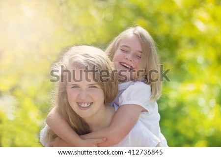 Front forward view, with focus on face of older girl, of sisters sharing a close moment while outdoors. Light haze effect applied to image.  - stock photo