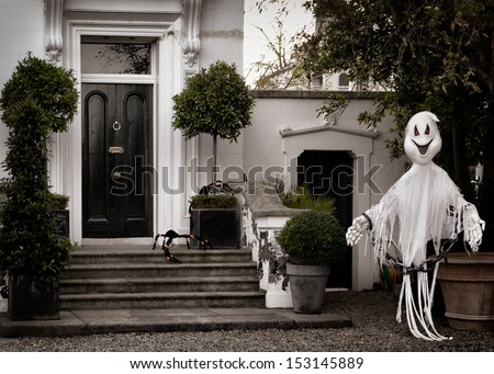 Front garden decoration for halloween with scary ghost big spiders - stock photo