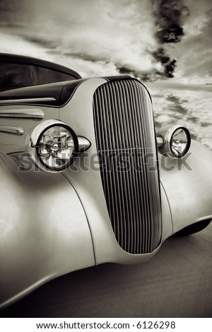 Front grill and headlight view of a restored 1936 chevy classic car done in a quadtone. - stock photo