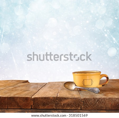 front image of coffee cup over wooden table in front of glitter background with glitter overlay  - stock photo