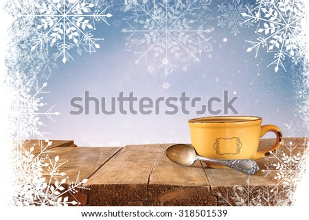 front image of coffee cup over wooden table in front of glitter background with snowflake overlay  - stock photo