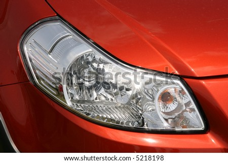 Front lamp of a new, orange, shiny car - stock photo
