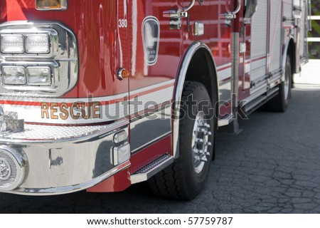 Front left close-up of shiny reflective red fire truck