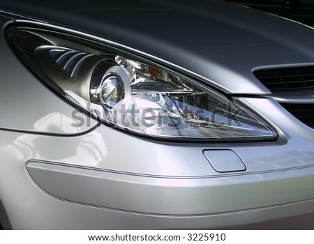 Front lights of silver German sports or expensive car - stock photo