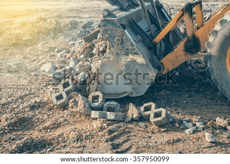 Front loader with mounted wide bucket loading concrete waste for recycling at building site.  Selective focus and vintage style. - stock photo