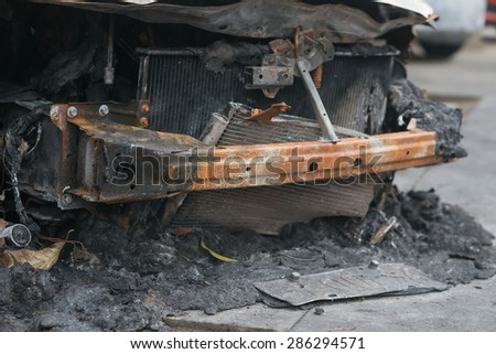 front of a burnt out car in an outdoor park