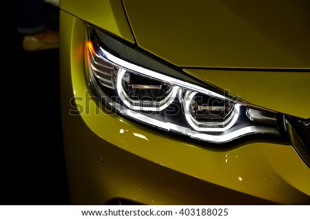 front of a car or vehicle model colora last yellow metal and a front light with the light and black background