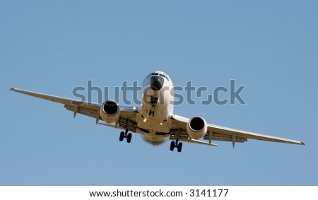 front of a commercial airplane under clear blue sky - stock photo