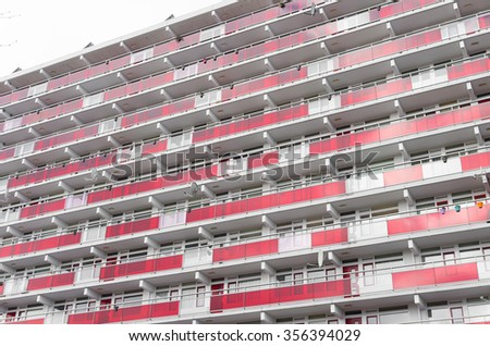 front of a large urban apartment building with red decorations - stock photo
