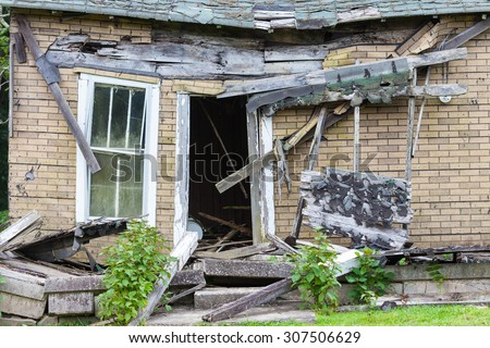 Front of an abandoned house that is falling down - stock photo