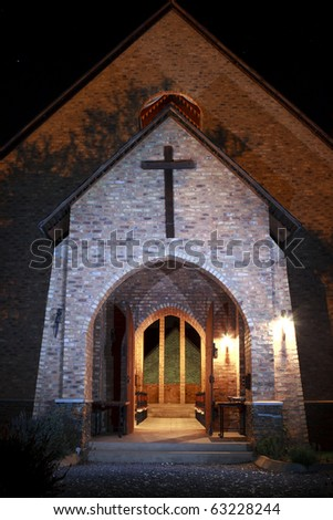 Front of church at night with beautiful lights and cross and open door - stock photo