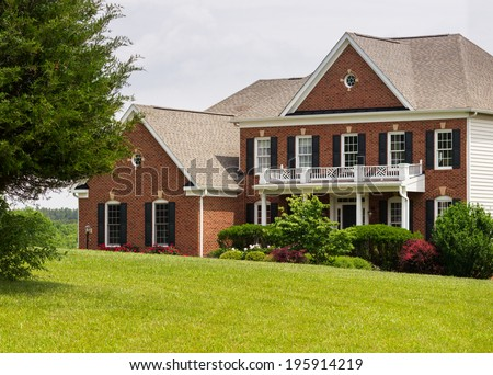 Front of home and garage of large single family modern US house with landscaped gardens and lawn on a warm sunny summers day - stock photo