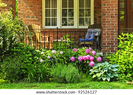 Front of home with chairs and flower garden - stock photo