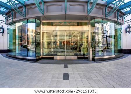 Front of luxurious apartment building, with glass windows and doors. - stock photo